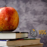 Banner image of an Apple, textbooks and a chalkboard background