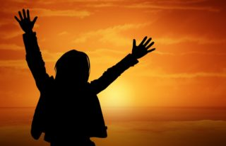 A woman with her hands up in the air with a sunset in the background