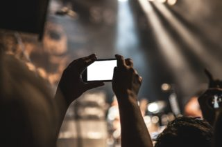 A person taking a picture at a concert with their smartphone